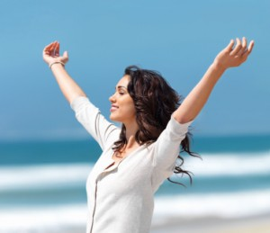 Kvinde-strækker-arme-imod-himlen-i-velbehag